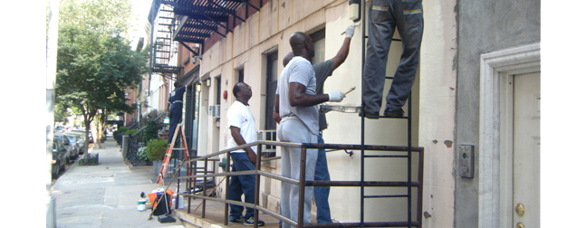 Volunteers paint the building facade